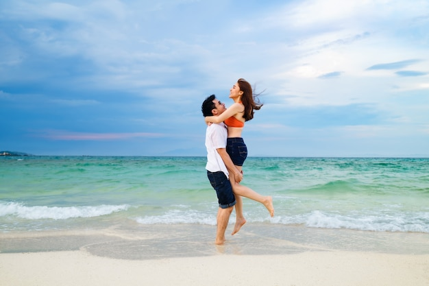 Young couple picking up and hugging on the sea beach at koh munnork island, rayong, thailand