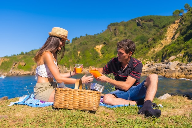 A young couple on a picnic in the mountains by the sea enjoying the summer