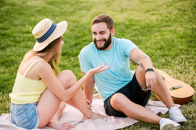 Young couple on the picnic in the park talking and relaxing