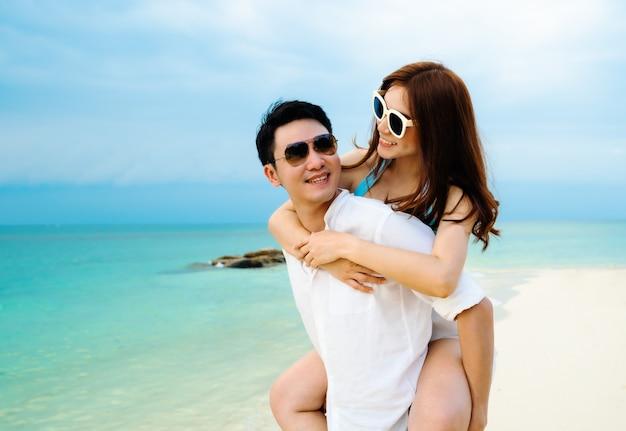 タイ、ラヨーン、コマンノーク島の海のビーチでピギーバックに乗る若いカップル
