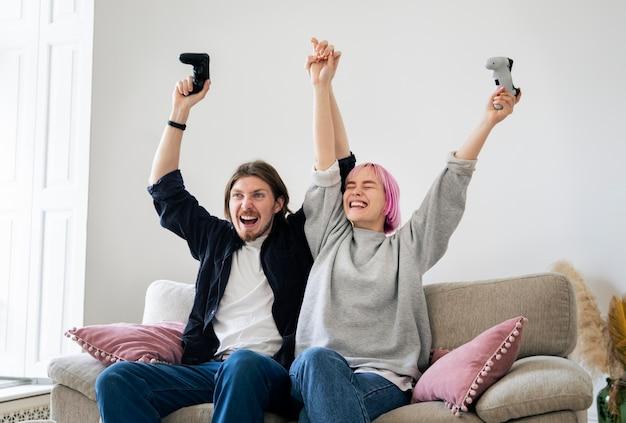 Молодая пара, играя в видеоигры дома