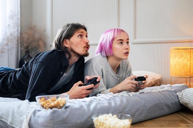 屋内でビデオゲームをしている若いカップル