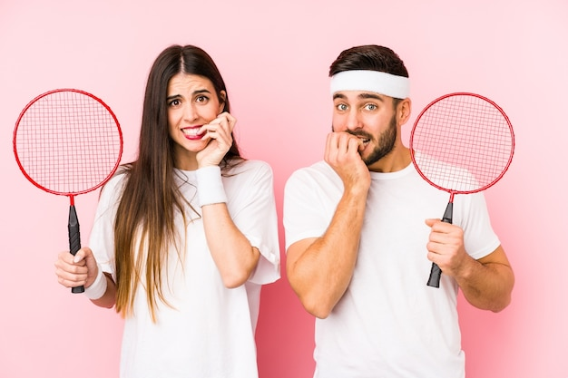 Young couple playing badminton isolated biting fingernails, nervous and very anxious.