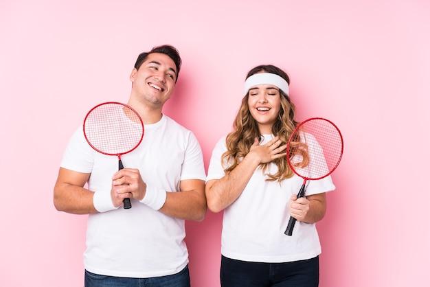 孤立したバドミントンをしている若いカップルは、胸に手を置いて大声で笑います。