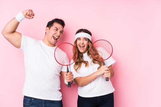 Молодая пара играет в бадминтон изолированно, поднимая кулак после победы
