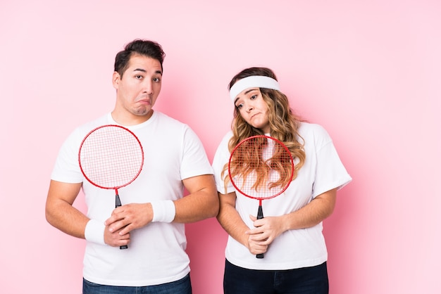 Young couple playing badminton shrugs shoulders and open eyes confused