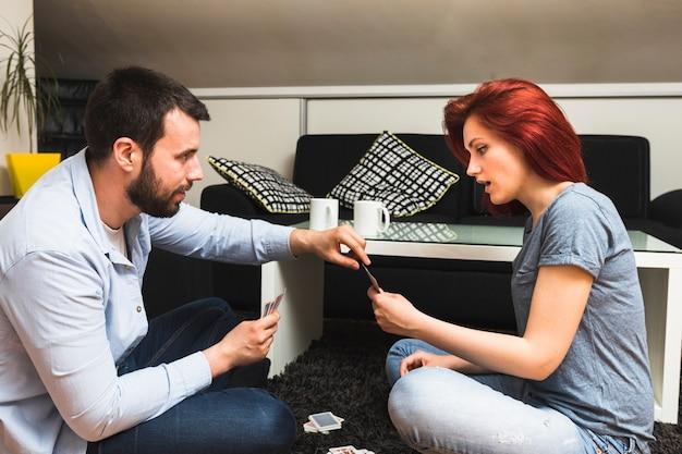 Молодая пара играть в карты дома