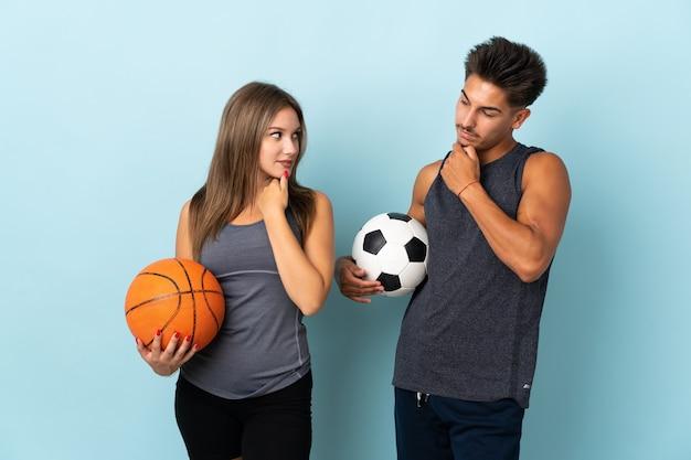 お互いを見て青でサッカーとバスケットボールをしている若いカップル