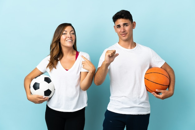 青の誇りと自己満足の概念でサッカーとバスケットボールをしている若いカップル