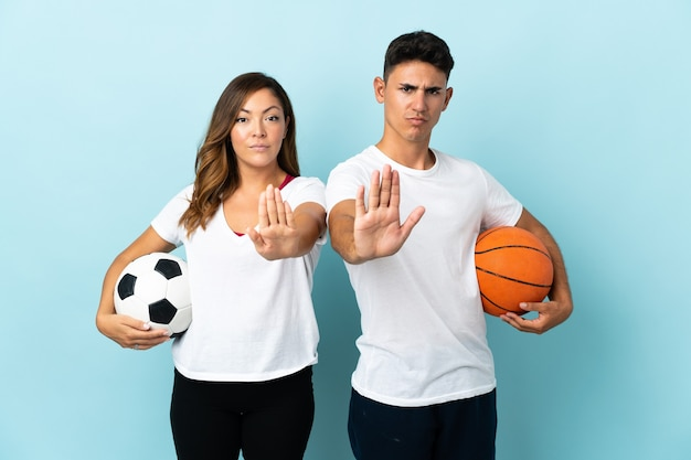 Young couple playing football and basketball on blue making stop gesture denying a situation that thinks wrong