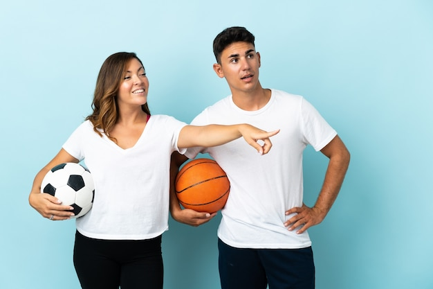 Young couple playing football and basketball on blue pointing to the side to present a product