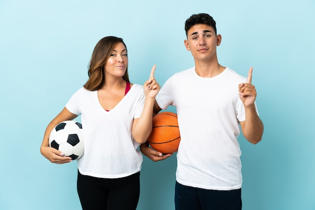 Young couple playing football and basketball on blue showing and lifting a finger in sign of the best