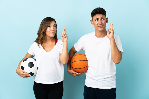 Young couple playing football and basketball on blue with fingers crossing and wishing the best