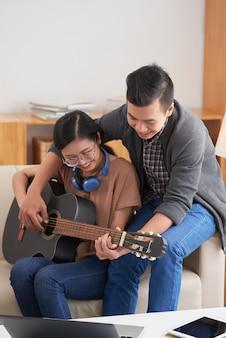 自宅でギターを弾く若いカップル