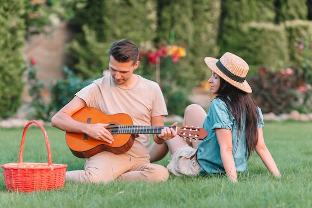 Young couple playing guitar on the grass