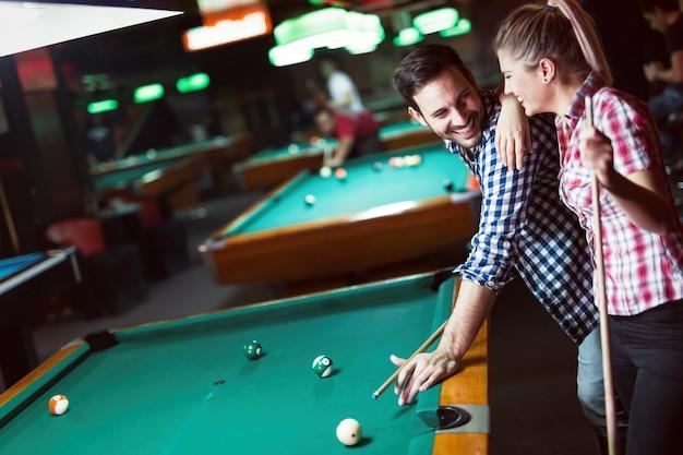 町で夜を過ごしながらバーでプールを遊んでいる若いカップル