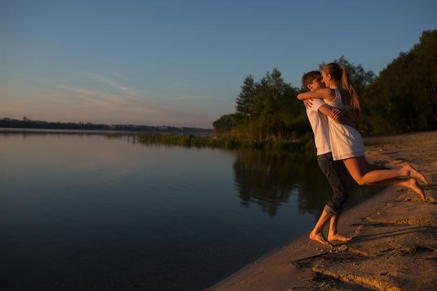 Giovani coppie che giocano sulla riva