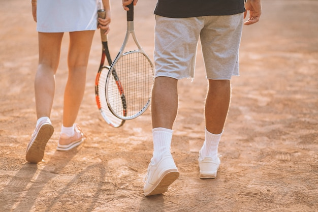 Young couple playing tennis at the court, feet close up