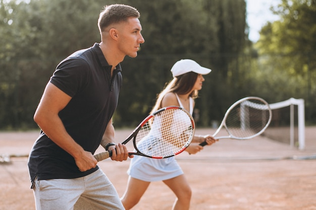 Young couple playing tennis at the court