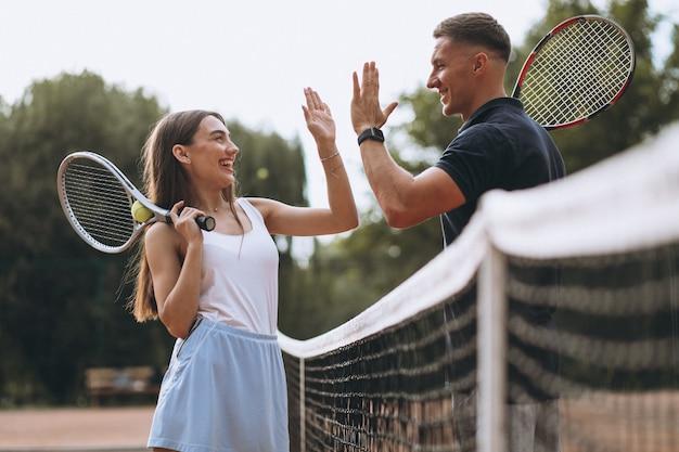 Giovani coppie che giocano a tennis alla corte