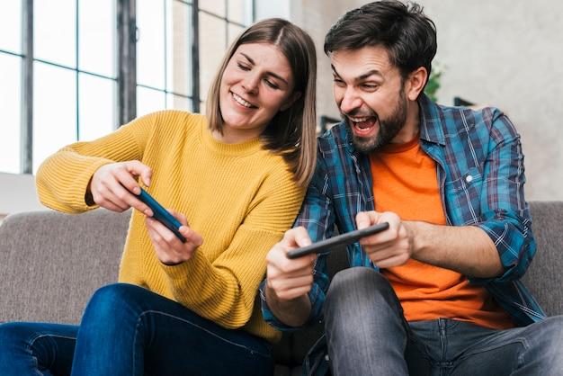 휴대 전화에 비디오 게임을하는 젊은 부부