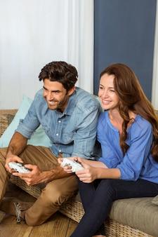 若いカップルがソファーに座りながらビデオゲームをプレイ