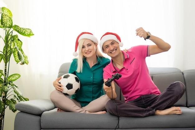 Молодая пара играет в видеоигры с джойстиками дома на рождество
