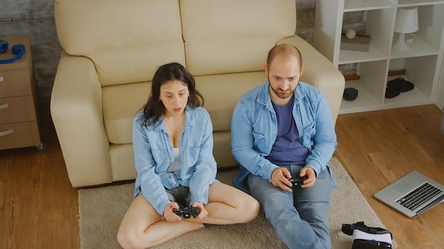 Молодая пара, играя в видеоигры с беспроводными контроллерами.