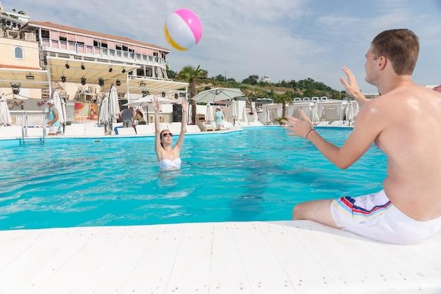 暑い夏の日にリゾートのプールで色とりどりのプラスチック製のビーチボールを互いに投げ合う若いカップル