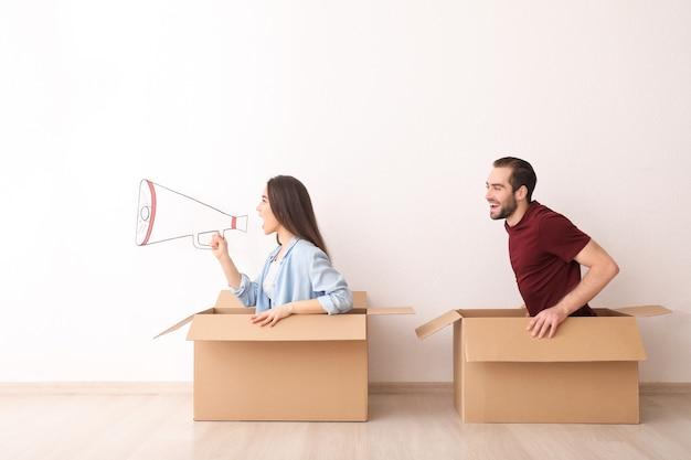 Молодая пара, играя с коробками в помещении. переезд в новый дом