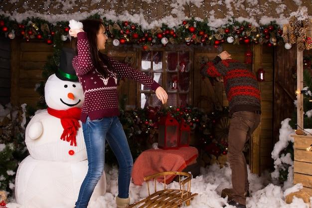 雪だるまとさまざまなクリスマスの装飾が施された木造住宅の中で綿の雪で遊ぶ若いカップル。