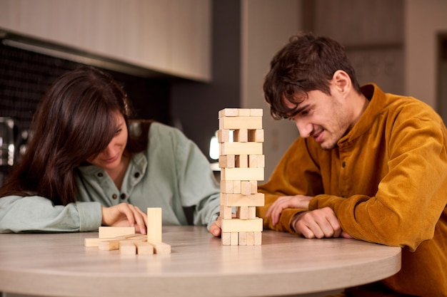 Young couple playing with wooden pieces on table while sitting in living room and have fun at home