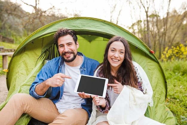 Молодая пара, указывая на таблетку в природе