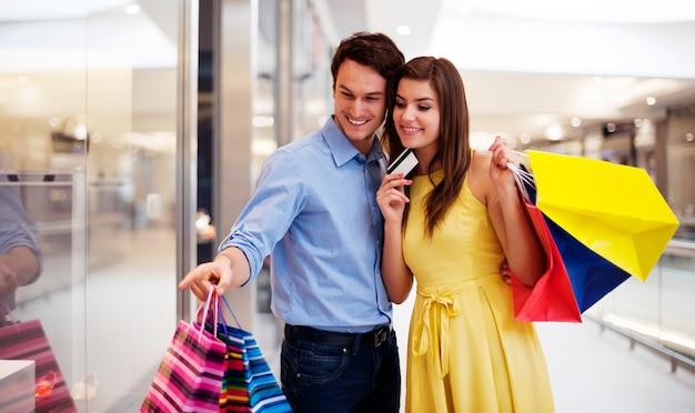 ウィンドウショッピングを指す若いカップル