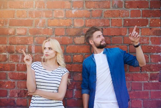 벽돌 벽에 가리키는 젊은 부부