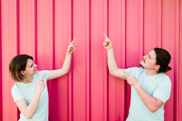 Young couple pointing their finger upward against corrugated iron sheet
