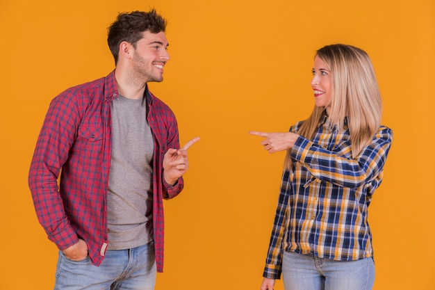 Young couple pointing their fingers to each other against an orange backdrop