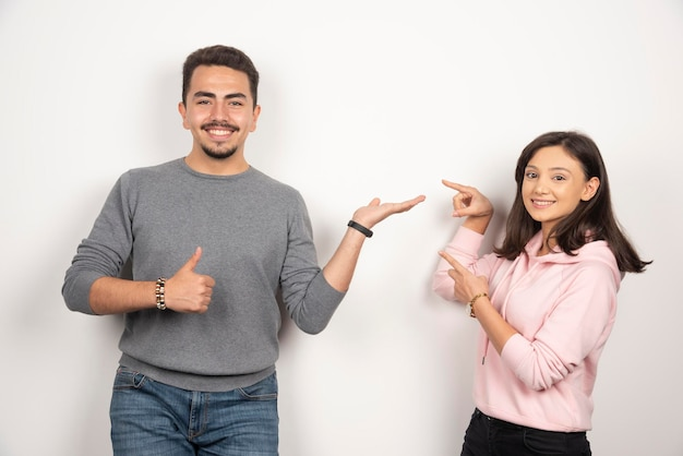 Giovani coppie che indicano se stessi su bianco.