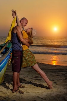 Young couple posing against sea at sunset. guy and girl fooling and grimace near the old wooden boat on the ocean coast