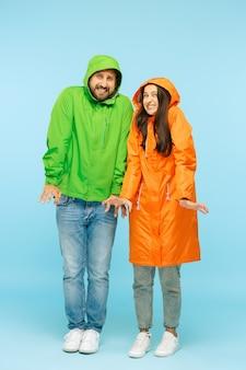 젊은 부부는 파란색에 고립 된가 자 켓에 스튜디오에서 포즈. 인간의 부정적인 감정. 추운 날씨의 개념. 여성 및 남성 패션 개념