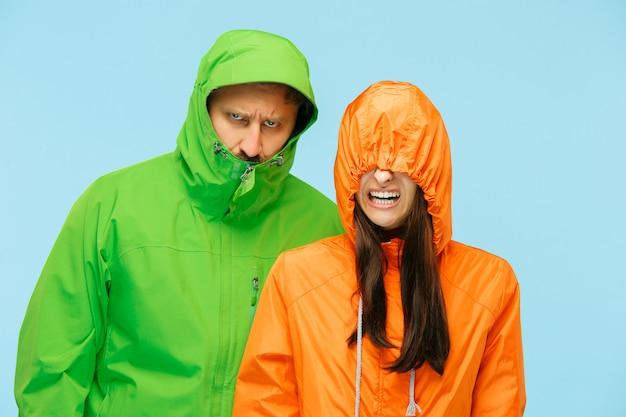 若いカップルが青に分離された秋のジャケットのスタジオでポーズ