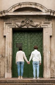 Coppia giovane in posa accanto a una porta
