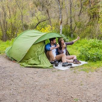 テントの近くでセルフのポーズをとっている若いカップル