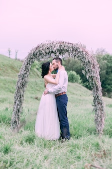 Молодая пара позирует для свадебной фотосессии летом