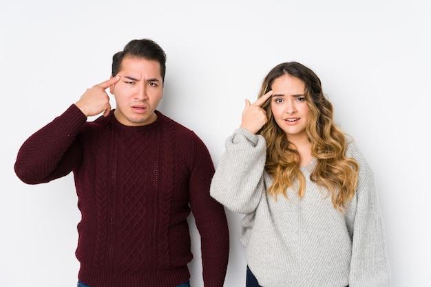 Молодые пары представляя в белой стене показывая жест разочарования с указательным пальцем.