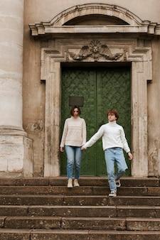 ドアの横でポーズをとる若いカップル