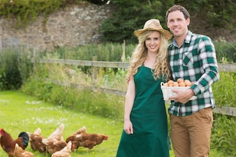 Young couple posing on a lawn holding a basket filled with eggs
