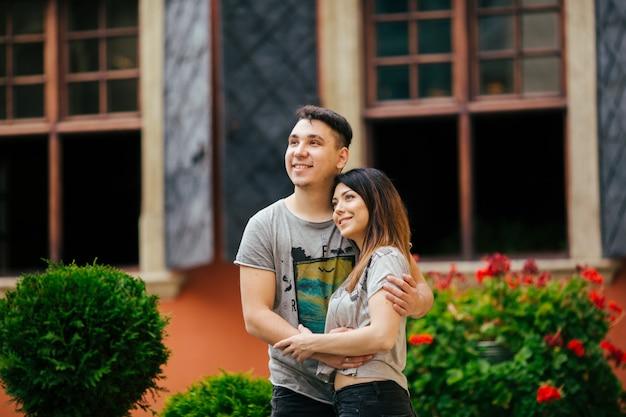 若いカップルが街背景旅行コンセプトでポーズ