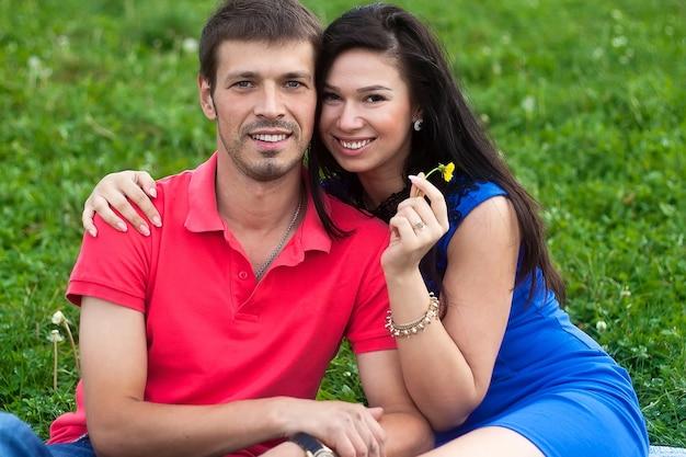 Молодая пара позирует на траве