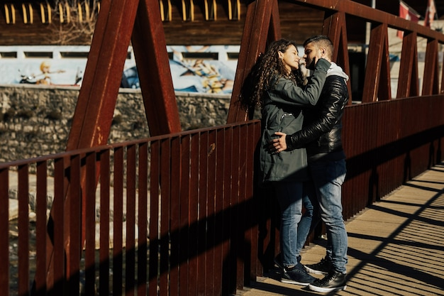 Young couple posing and talking on the old red metal bridge.